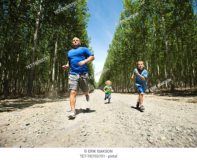 Father with sons 2-9 running down country road