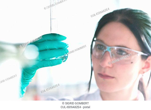 Close up of female scientist examining at test tube