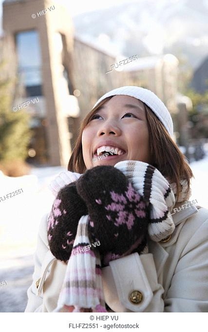 Portrait of smiling woman in toque, scarf and mitts, Whistler Village, Whistler, British Columbia
