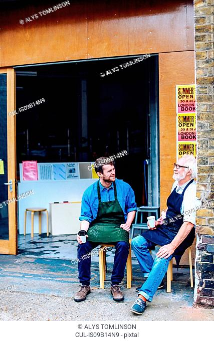 Senior craftsman drinking coffee and chatting to young man outside workshop