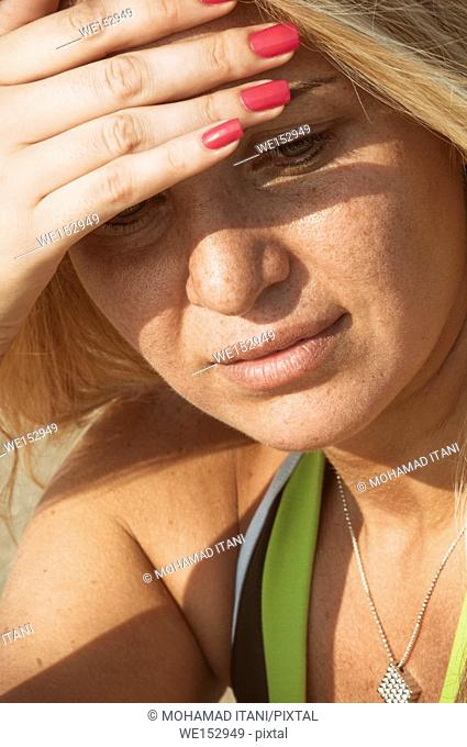 Serious blond woman hand covering eyes