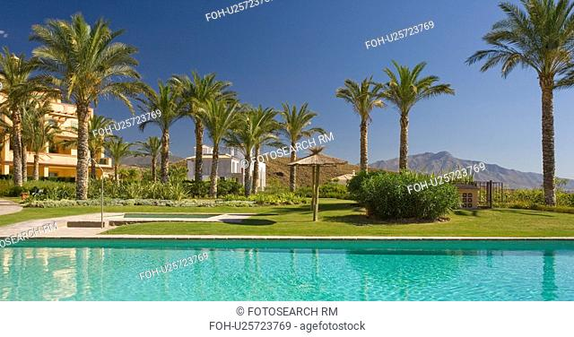 Rectangular turquoise swimmingpool and palm trees in front of apartment building in southern Spain