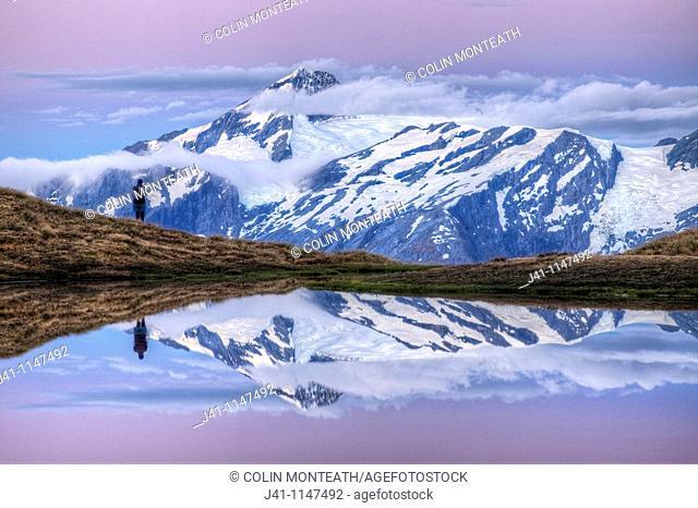 Mt Aspiring, tramper enjoys moonrise at dusk, Cascade Saddle tarn, Mount Aspiring National Park, Otago, New Zealand