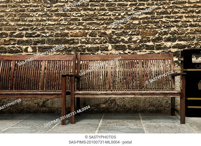 Benches in front of a weathered wall, Oxford, Oxfordshire, England