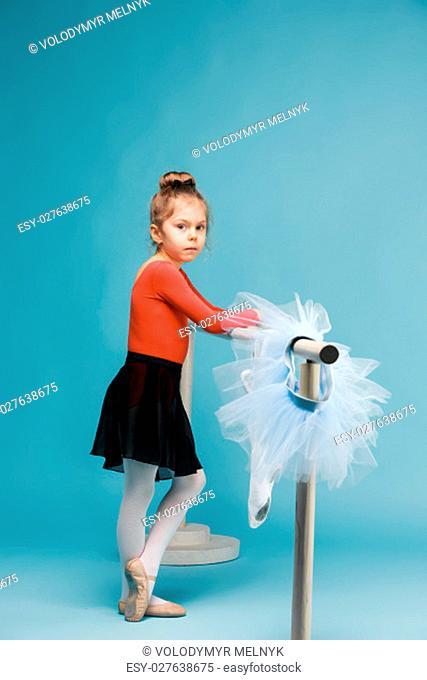The little girl as balerina dancer posing near ballet rack on blue studio background