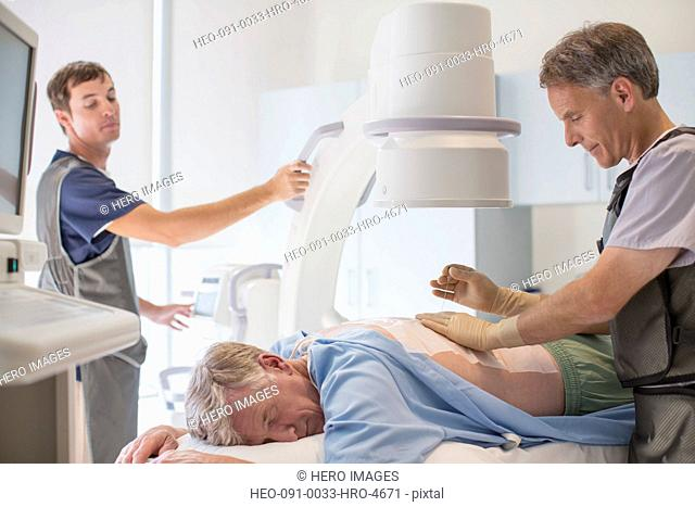 x-ray technicians prepping senior man for back x-ray