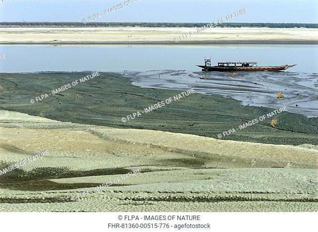 View of riverbank and river with low water levels, with stranded boat, River Brahmaputra, Kaziranga N.P., Assam, India, January