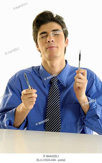 Businessman sitting at a desk and holding two pens