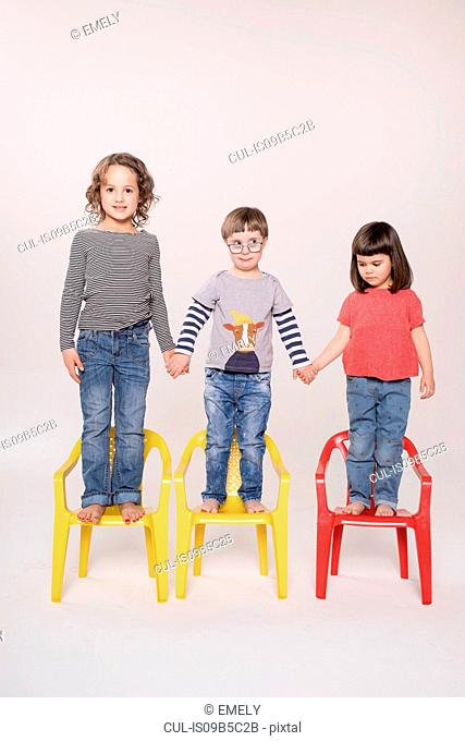 Portrait of three children standing on colourful chairs, holding hands, studio shot