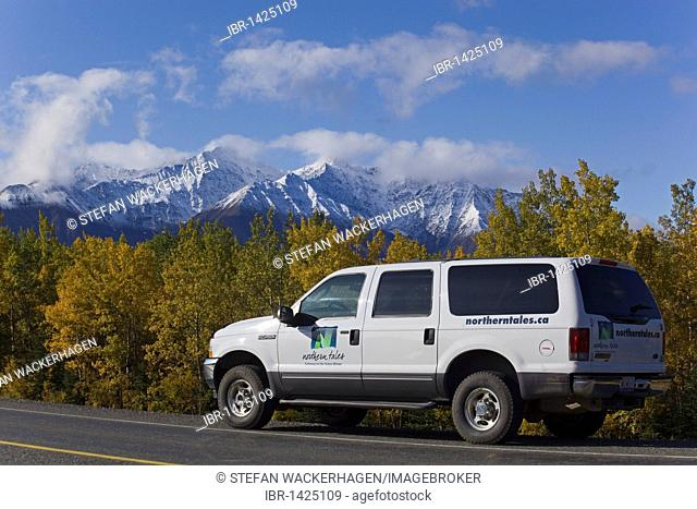 SUV driving along Alaska Highway, Indian Summer, trees in fall colours, St. Elias Mountains behind, Kluane National Park and Reserve, Yukon Territory, Canada