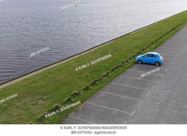 Solitary car, Fiat 500 parked in an empty parking lot on an inland waterway, Walcheren, Zeeland province, The Netherlands