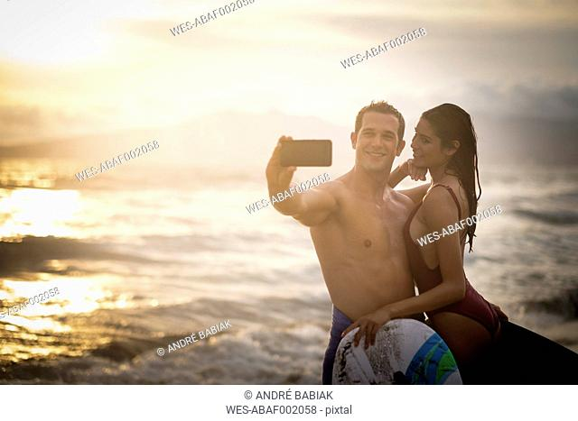 Young couple taking a selfie on beach at twilight