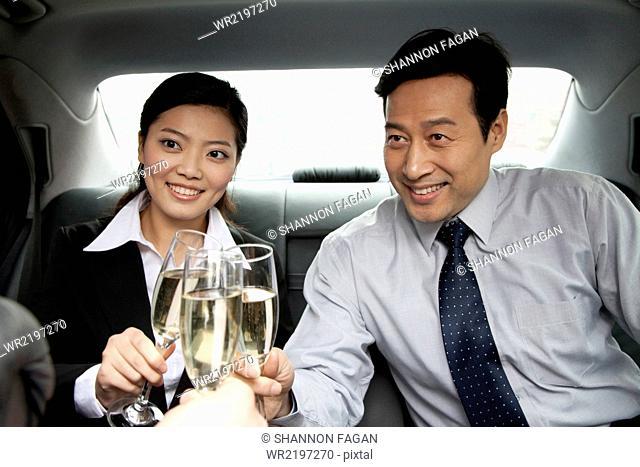 business people toasting in car