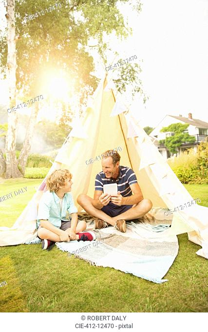 Father and son using digital tablet in teepee in backyard