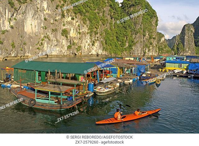 Kayaking past a floating fishing village in Halong Bay. Fish farm village amongst karst limestone mountains at Cat Ba National Park, Ha long,Halong Bay, Ha long
