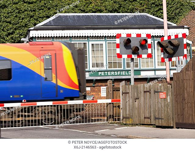 Train passing Petersfield 1880's Type 3 Signal Box with down full barrier type level crossing