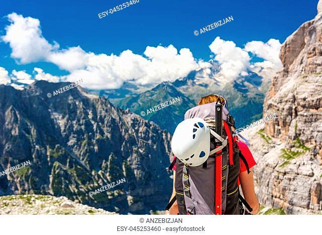 Female trekker walking along mountain valley. Trekking Brenta Dolomites, Sentiero delle Bocchette Alte