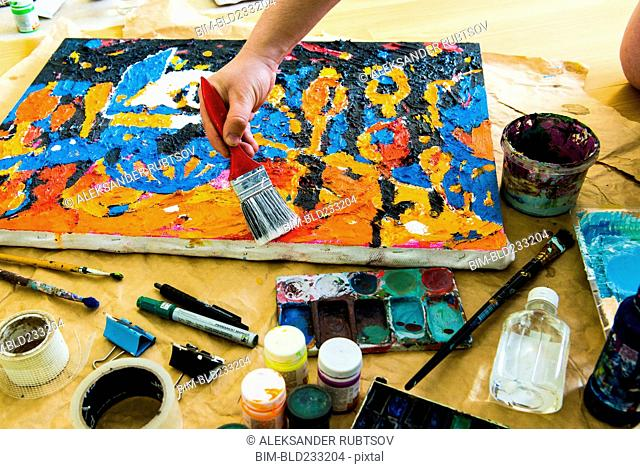 Hand brushing paintbrush over canvas painting