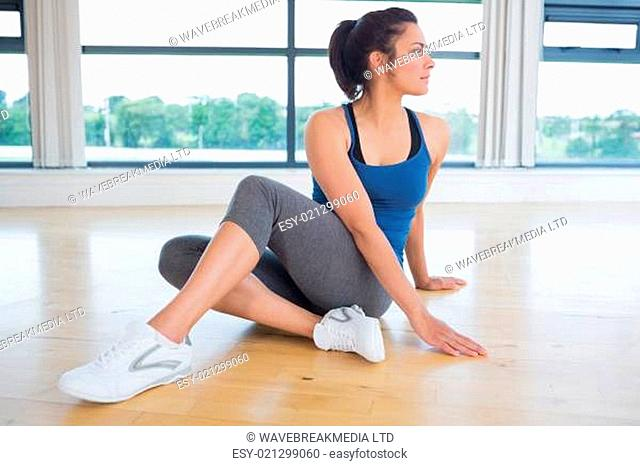 Woman concentrating on yoga pose in fitness studio