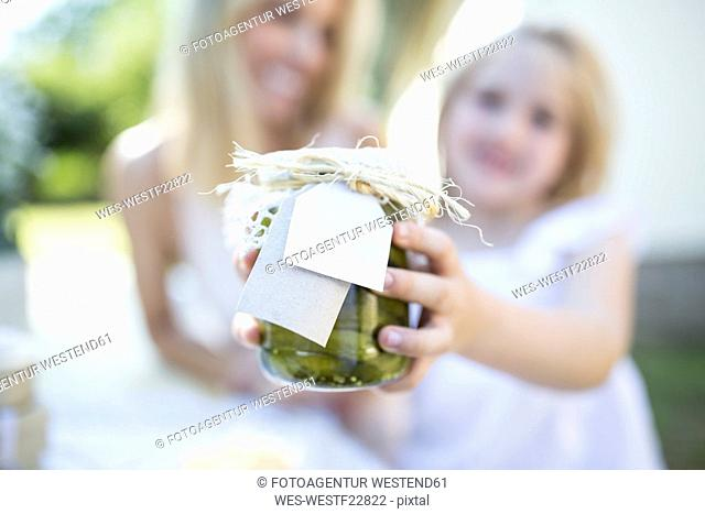 Mother and daughter holding jar with preserved gherkins outdoors