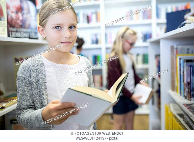 Portrait of smiling schoolgirl with book in school library