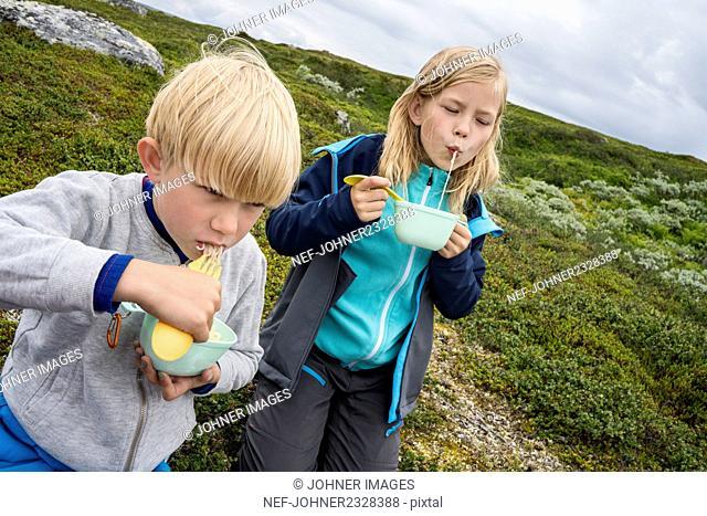 Kids eating noodles