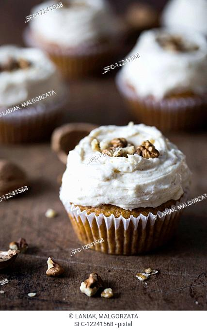 Pumpkin cupcake with cream cheese frosting and walnuts