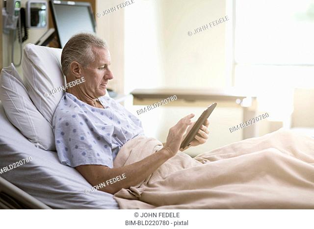 Caucasian patient using digital tablet in hotel bed