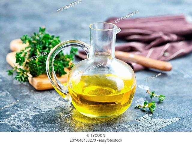 thyme oil in glass jug and on a table