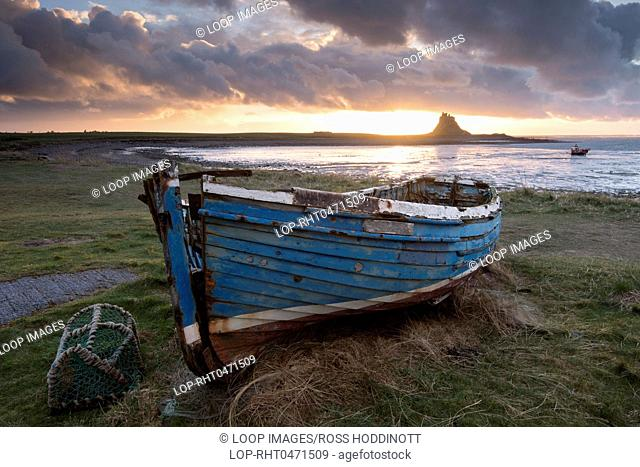 Fishing boat and view looking toward Lindisfarne castle at dawn on Holy Island