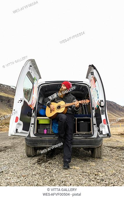 Iceland, man in front of van playing guitar