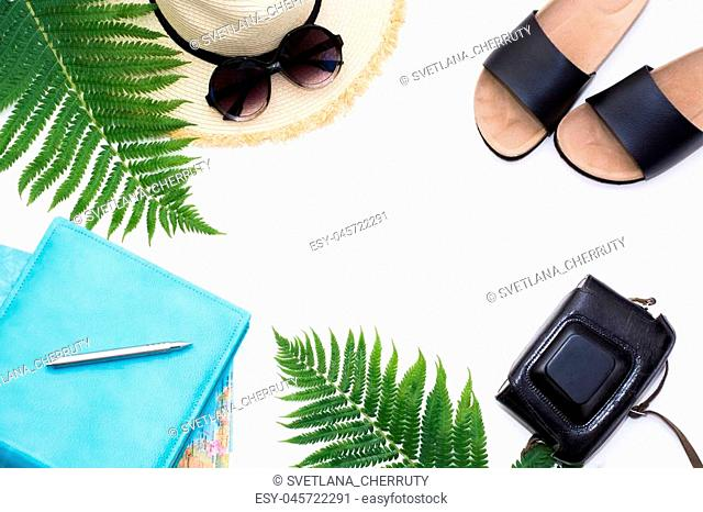 Tropical vacation planing. Straw beach sunhat, sun glasses, map, camera, leaf of fern on white background. Top view with copy space. Summer