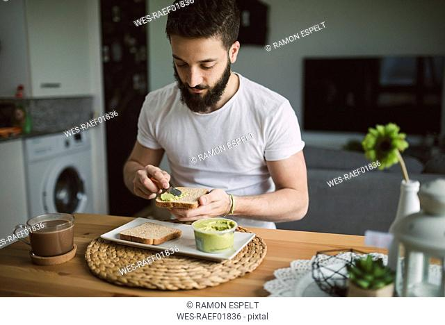 Young man having breakfast at home, toast with avocado cream