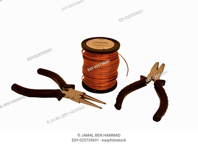 Spool of copper wire and tools on a white background.