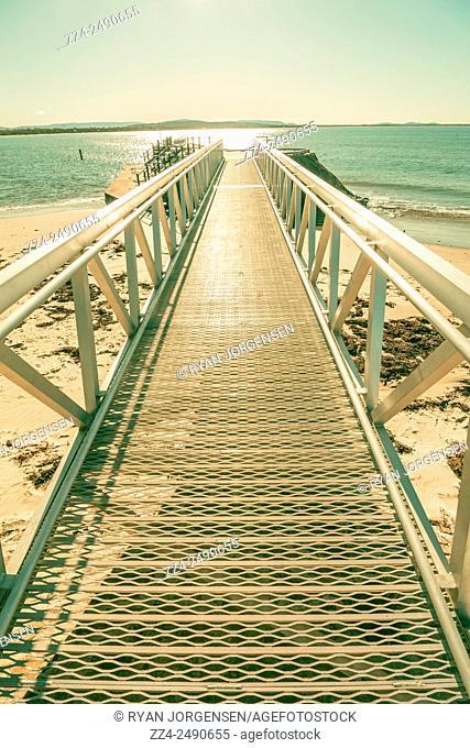 Pastel toned modern metal pier promenade protruding out over a sea shore. Swansea, Tasmania, Australia