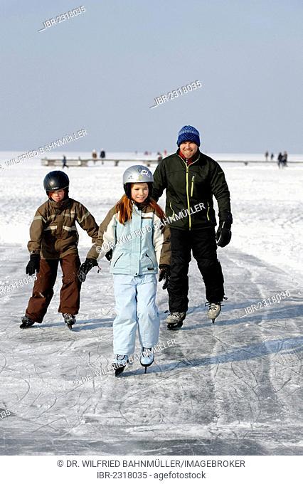 Familiy ice skating near St. Heinrich, Lake Starnberg, Five Lakes region, Upper Bavaria, Bavaria, Germany, Europe