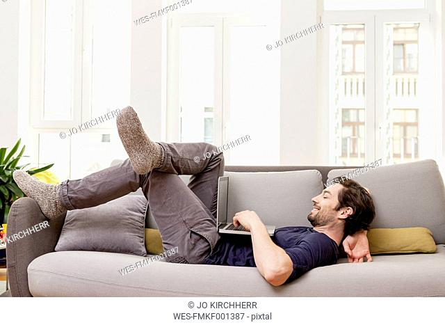 Relaxed man lying on couch using laptop