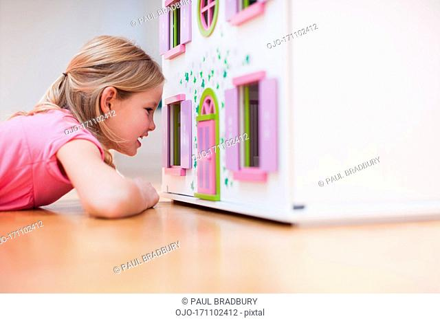 Girl peering into dollhouse