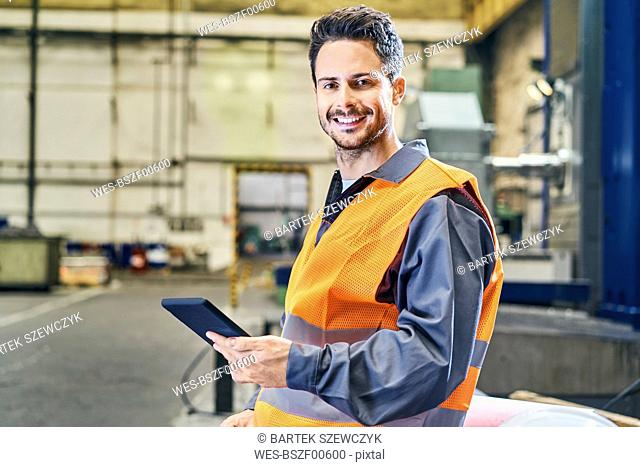 Portrait of smiling man holding tablet in factory
