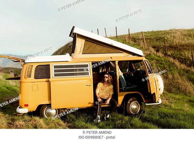 Young male skateboarder looking out from vintage recreational vehicle, Exeter, California, USA