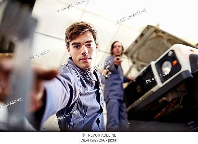 Mechanic reaching for tool below car in auto repair shop