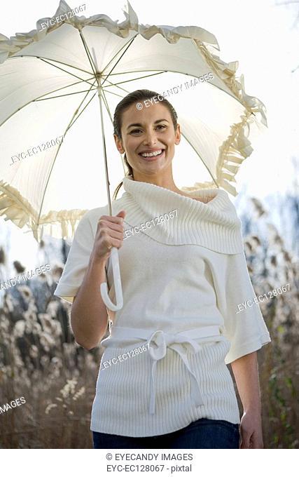 Beautiful young woman enjoying with umbrella in field