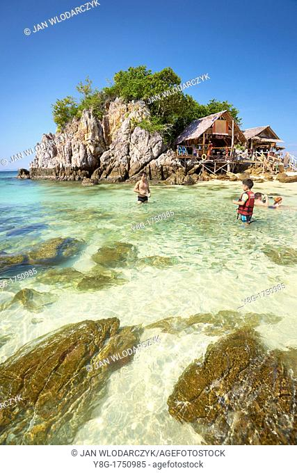 Thailand - Khai Island, Phang Nga Bay, turists feeding fish in the turquoise water at the shore