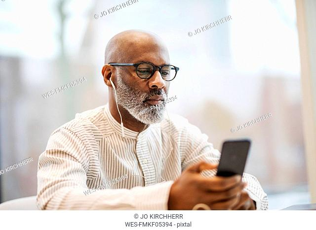 Portrait of mature businessman using smartphone and earphones