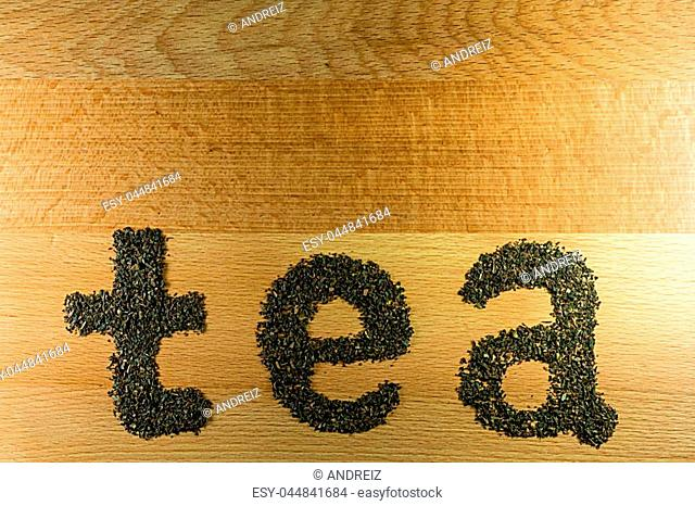 The word tea is laid out on a light-brown wooden Board small leaf black tea. Board is the background for the word tea