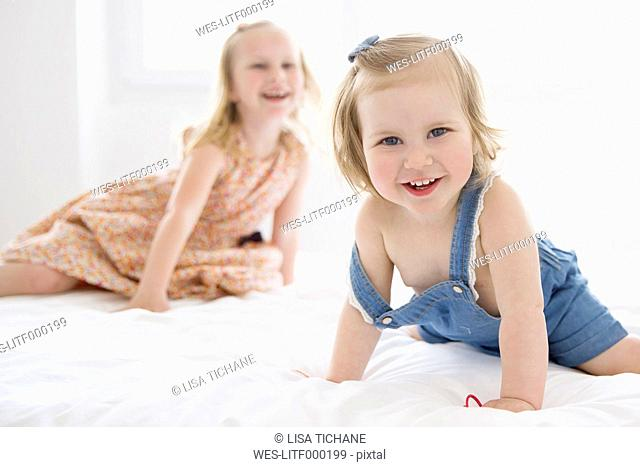 Portrait of smiling toddler girl on a white bed with her sister in the background