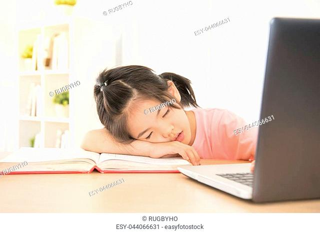 pink clothes schoolchild feeling tired sleeping on book in front of computer in the room. sleepy asian kids face down in front of the laptop at home