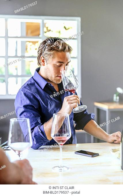 Caucasian man smelling wine in restaurant