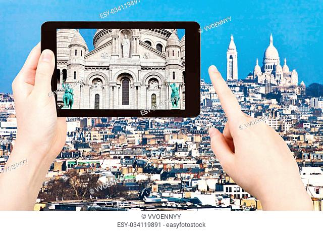 travel concept - tourist taking photo panorama of montmartre hill and basilique sacre coeur in Paris on mobile gadget, France