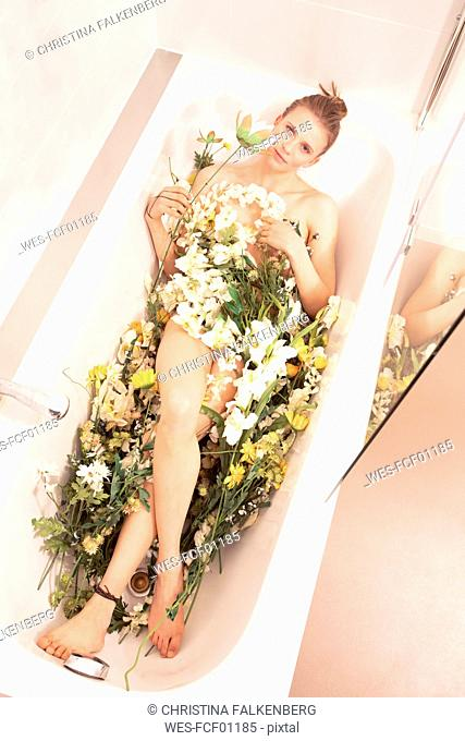 Young woman lying in flower bath